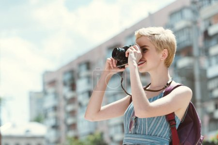 young woman taking photo on camera in city