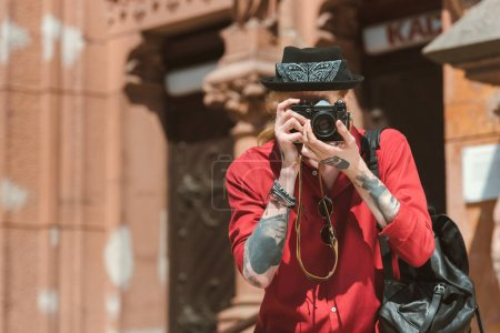 tattooed man with backpack taking photo on camera