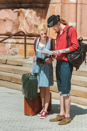 couple of travelers with backpacks and retro suitcases looking at map