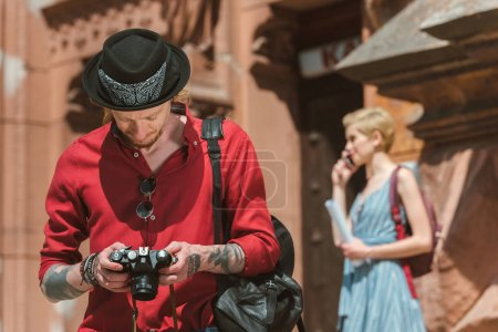 man looking at photo camera while girlfriend standing behind