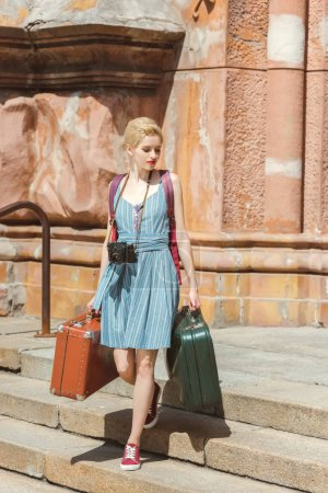 beautiful traveler with camera and retro suitcases