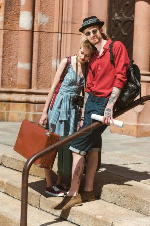 beautiful couple of tourists with vintage travel bags hugging in city