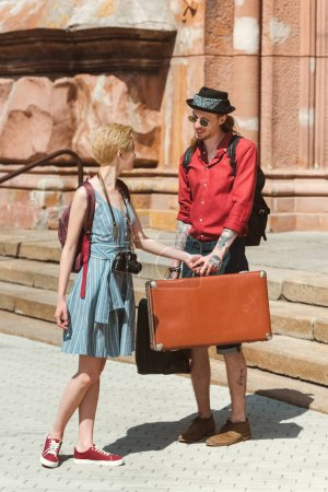 couple of travelers with vintage suitcases in city