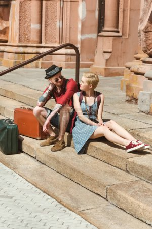 couple of travelers with vintage suitcases sitting on stairs in city