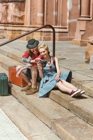 Photo for Couple of travelers with vintage suitcases sitting on stairs and looking at camera - Royalty Free Image