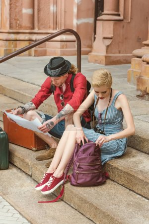 couple of travelers with backpacks and vintage suitcases sitting on stairs and looking at map