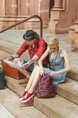 """Постер, картина, фотообои """"пара путешественников с рюкзаками и винтажные чемоданы, сидя на лестнице и, глядя на карте"""""""