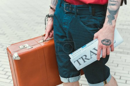 partial view of man with travel newspaper and vintage suitcase