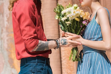 cropped view of couple with flowers on romantic date