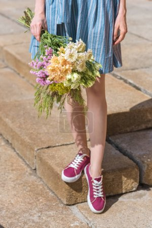 cropped view of girl holding bouquet of flowers
