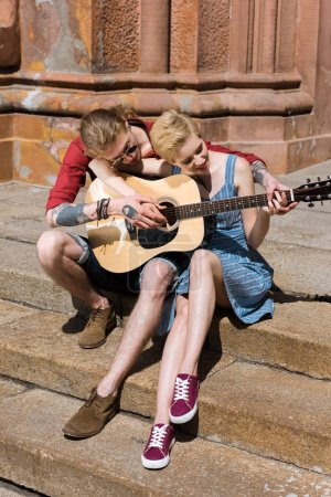 beautiful couple playing acoustic guitar together in city
