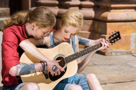 Photo for Young couple playing acoustic guitar together - Royalty Free Image