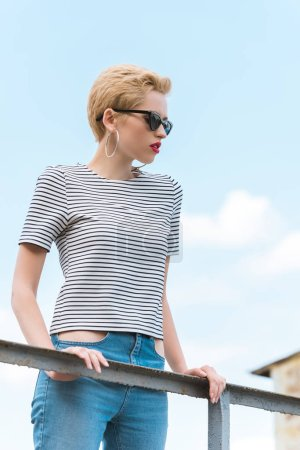 stylish girl in sunglasses and with short hair leaning on railing
