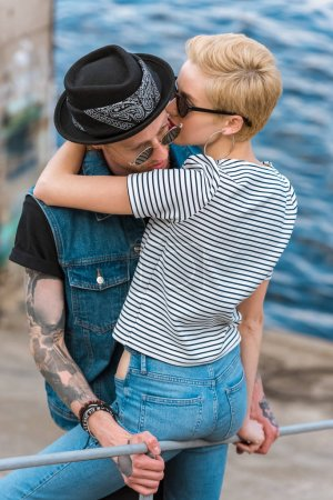 boyfriend with tattoos and stylish girlfriend hugging and leaning on railing near river