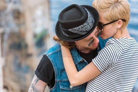 boyfriend with tattoos and stylish girlfriend cuddling near river
