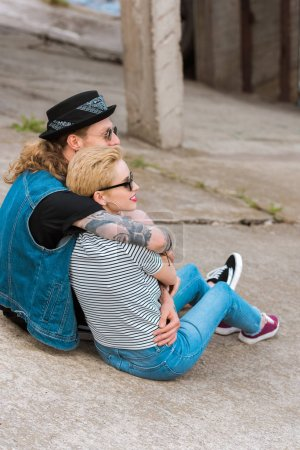side view of boyfriend with tattoos hugging stylish girlfriend and they looking away