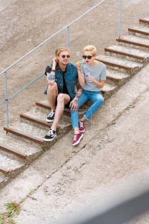 high angle view of girlfriend and boyfriend sitting on stairs and having fun with soap bubbles
