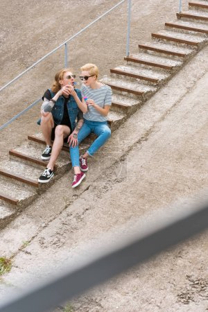 high angle view of stylish couple sitting on stairs and having fun with soap bubbles