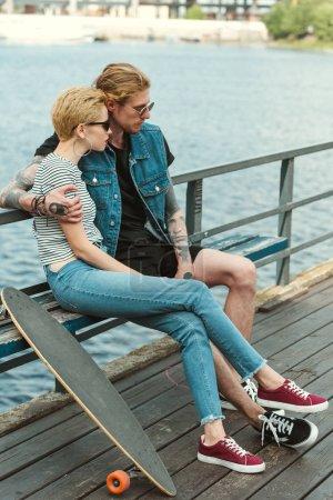 stylish couple sitting on bench on bridge and looking away