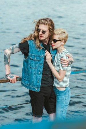 boyfriend with tattoos and stylish girlfriend hugging on bridge near river