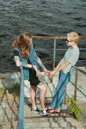 high angle view of boyfriend with tattoos and stylish girlfriend holding hands and looking at each other near river