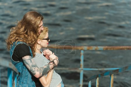 side view of boyfriend with tattoos hugging stylish girlfriend on bridge near river