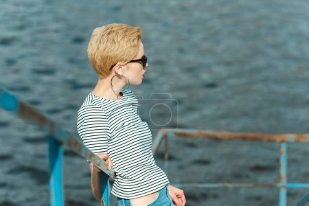stylish girl in sunglasses leaning on railing near river and looking away