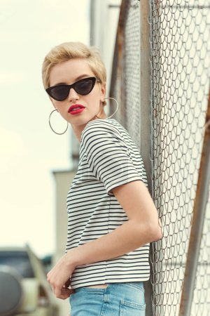 stylish girl in sunglasses looking away through fence