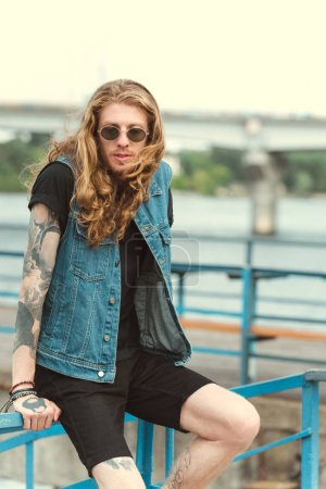 handsome stylish tattooed man sitting on railing of bridge