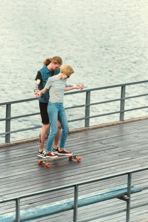 high angle view of boyfriend with tattoos teaching skating stylish girlfriend
