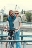 """Постер, картина, фотообои """"бойфренд с Татуировки и стильная девушка позирует возле велосипедов на мосту"""""""