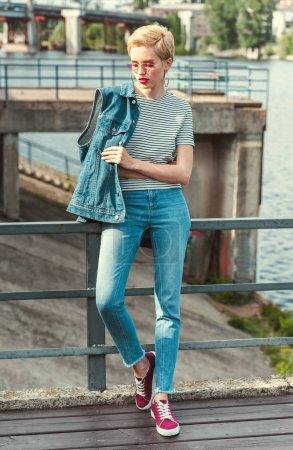 Photo pour Élégante jolie jeune fille debout sur le pont en jeans et veste de denim - image libre de droit