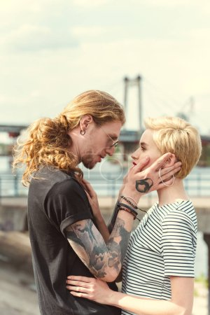 boyfriend with tattoos and stylish girlfriend looking at each other on bridge