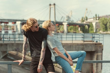 boyfriend with tattoos and stylish girlfriend touching with backs and sitting on railing of bridge