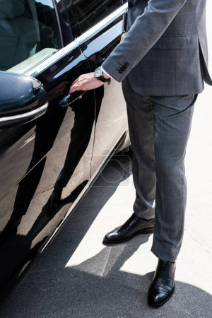 cropped shot of businessman opening car door