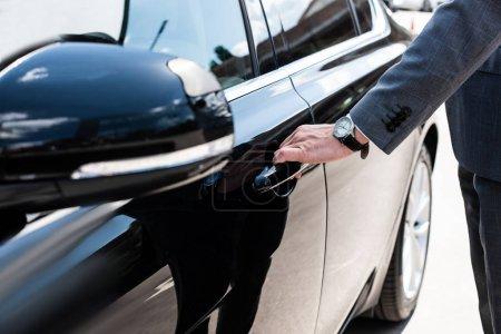 Photo pour Vue partielle de l'homme d'affaires, ouverture de porte de voiture - image libre de droit