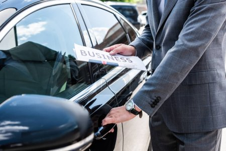 cropped shot of businessman with newspaper opening car door on street