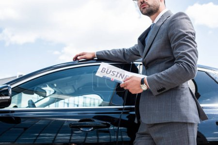partial view of businessman with newspaper standing at car on street