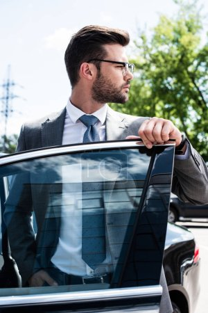 portrait of thoughtful businessman looking away while standing at car on street