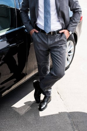 partial view of businessman with hands in pockets standing at car on street