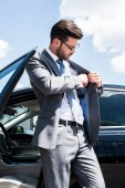 businessman taking something out pocket while standing near car on street