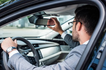 side view of businessman checking back view while driving car