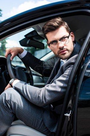 pensive businessman in eyeglasses looking away while sitting in car
