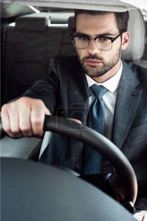 portrait of businessman in eyeglasses driving car alone