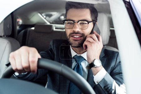 portrait of smiling businessman talking on smartphone while driving car