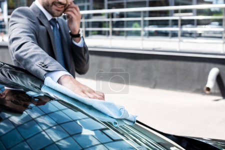 Photo for Partial view of smiling businessman talking on smartphone while cleaning front glass with rag - Royalty Free Image