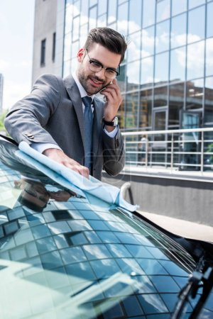 smiling businessman talking on smartphone while cleaning front glass with rag