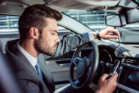 side view of businessman using smartphone while driving car