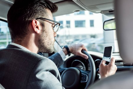 businessman using smartphone while driving car