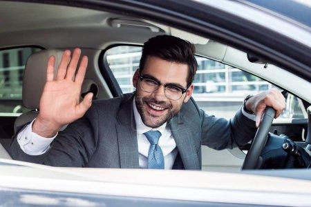 Photo pour Vue latérale de l'homme d'affaires joyeux saluant quelqu'un tout en conduisant une voiture - image libre de droit